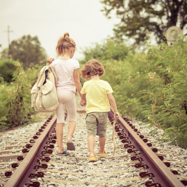 two little kids with backpack standing on the railway